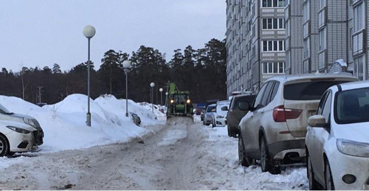 Трактор чистит дорогу от снега во дворе жилого дома